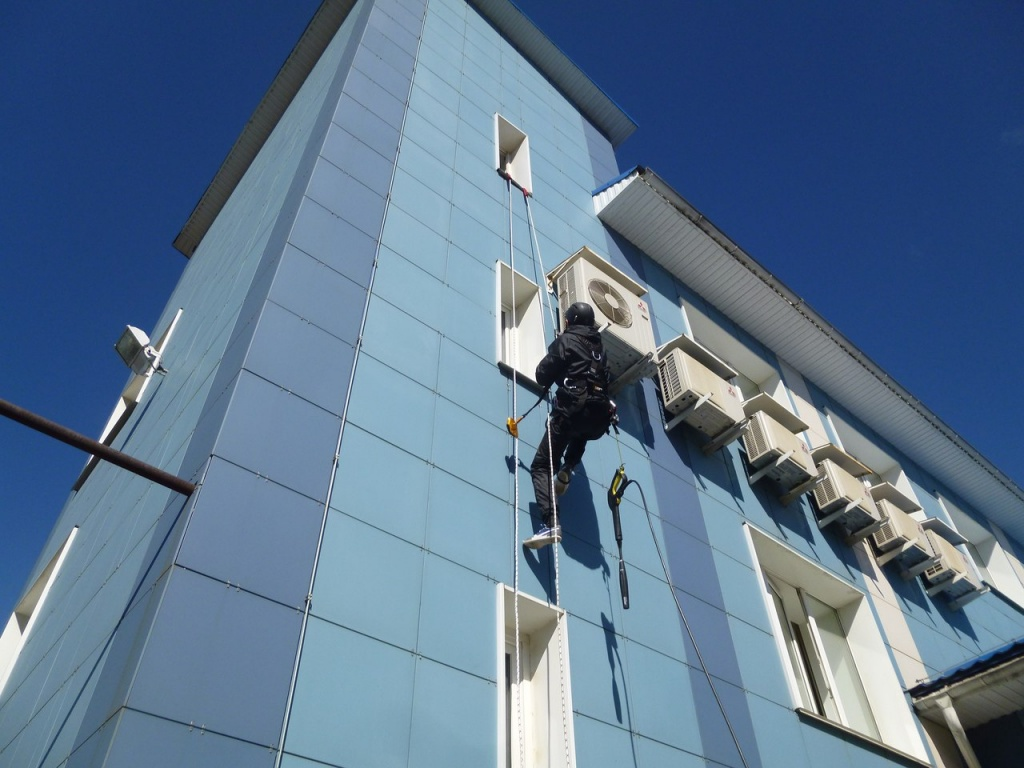 Рабочий чистит фасад здания.jpg